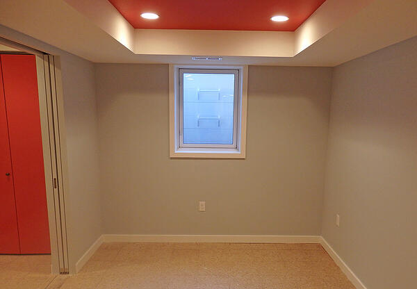basement bedroom with coffered ceiling and exit window