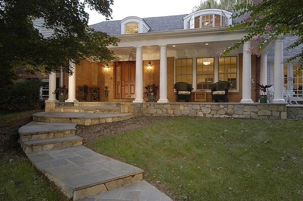 front entry porch with stone base and white pillars