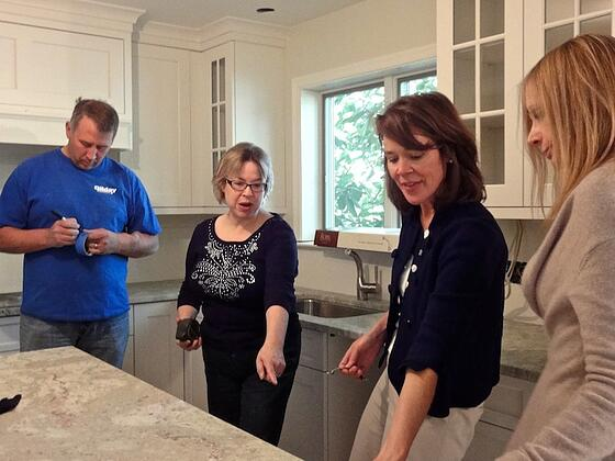 interior designers meet with client on site of design build kitchen remodeling project