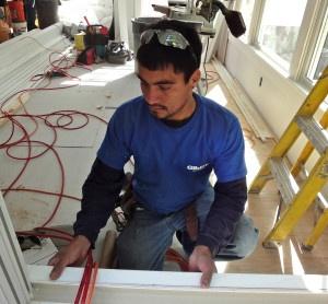 carpenter fits window trim to home-addition-under- construction